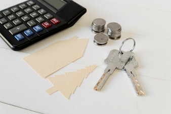 Calculator; coins stack; keys with house and tree paper cutout on white wooden table