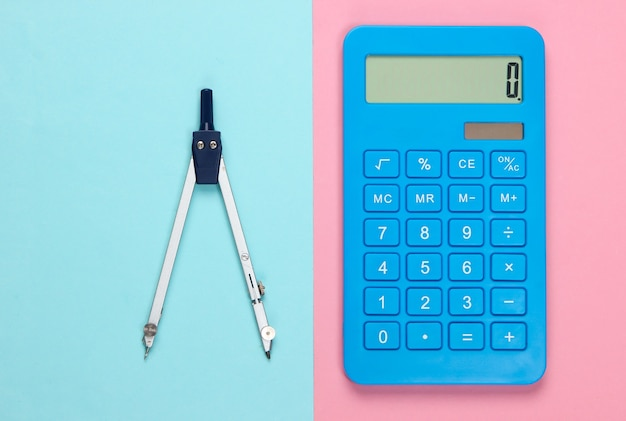 Calculator and compass on pink blue pastel.
