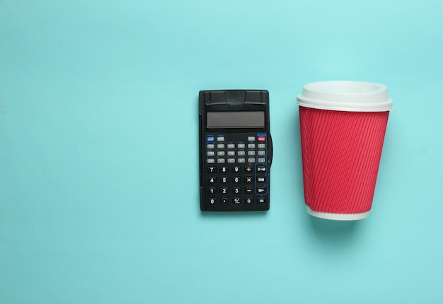 Calculator and cup coffee on blue background