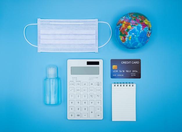 電卓、地球、マスク、クレジットカード、ノート、青の背景にアルコールゲル消毒剤。コロナウイルスが収入と経済に及ぼす影響。