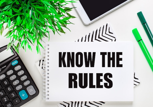 계산기, 녹색 식물, 전화, 마커, 노트북에 데스크탑에 규칙을 알고 있습니다. 평평하다.