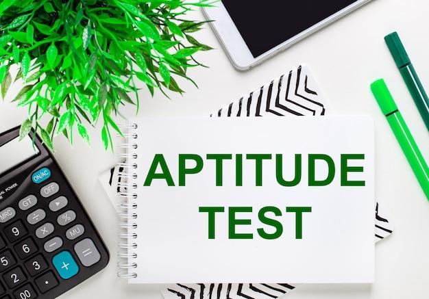 Калькулятор, зеленое растение, телефон, маркер, блокнот с текстом тест аппитуды на рабочем столе.