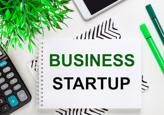 Калькулятор, зеленое растение, телефон, маркер, блокнот с текстом бизнес-стартап на рабочем столе. плоская планировка.