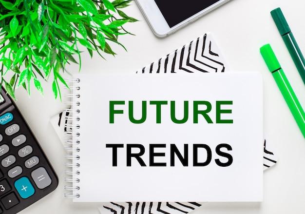 Калькулятор, зеленое растение, телефон, маркер, блокнот с текстом будущие тенденции на рабочем столе. плоская планировка.