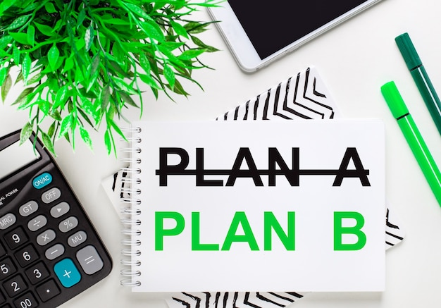 Калькулятор, зеленое растение, телефон, маркер, блокнот с текстом план б на рабочем столе