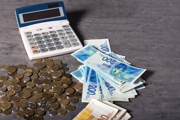 계산기, 이스라엘 셰켈 메모 및 동전, 테이블에 100 및 200 교단의 지폐. 모든 디자인을 위한 공간을 복사합니다. 10, 50 agorot의 흩어져있는 동전, 이스라엘 one 새로운 셰켈 동전. 확대
