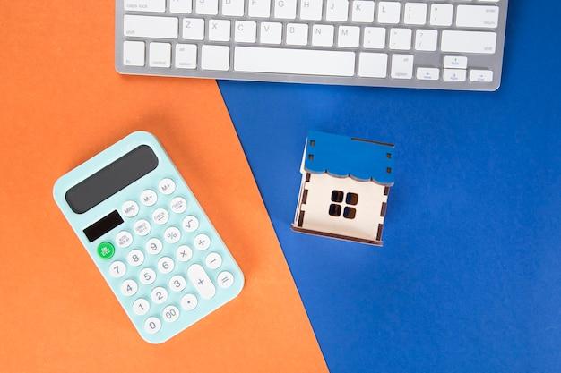 Калькулятор, клавиатура и домик. концепция расчета стоимости дома