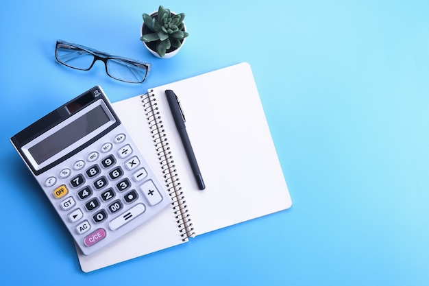 青い背景の電卓キーパッド。ノートブック、ペン、メガネ、デスクトップ。財務トップビュー。コピースペース
