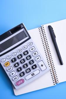 青いテーブルの電卓キーパッド。ノートブック、ペン、メガネ、デスクトップ。財務トップビュー。コピースペース