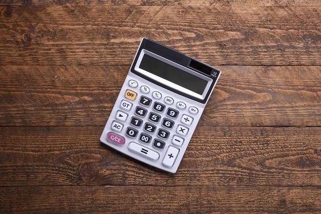 木製の床の背景に電卓のキーパッド。上面図。コピースペース