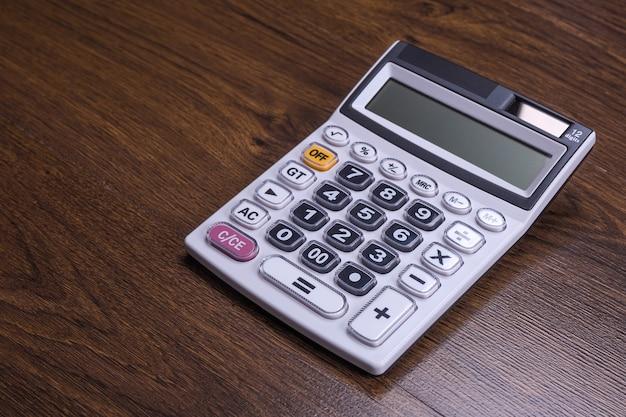 Клавиатура калькулятора на фоне деревянного пола. вид сверху. копировать пространство