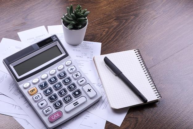 木の床の背景で買い物から店からの小切手が付いている電卓のキーパッド。上面図。コピースペース