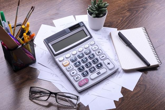 Клавиатура калькулятора с чеками из магазина от покупок на фоне деревянного пола. вид сверху. скопируйте пространство.