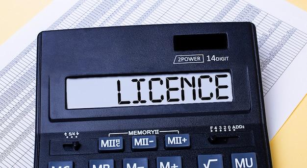 Калькулятор с надписью лицензия на столе рядом с отчетом. финансовая концепция