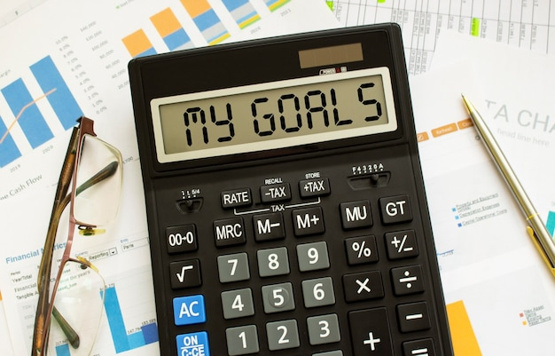 A calculator labeled my goals lies on financial documents in the office. business concept.