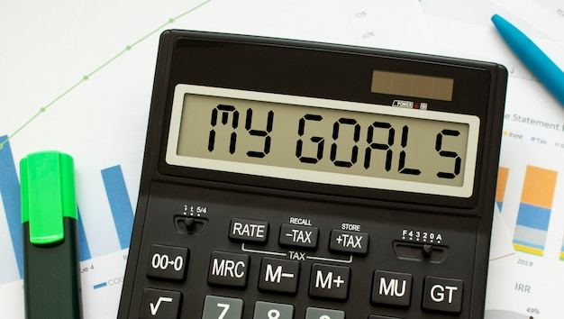 A calculator labeled my goals lies on financial documents in the office.
