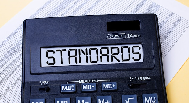 A calculator labeled standards is on the table near the report.
