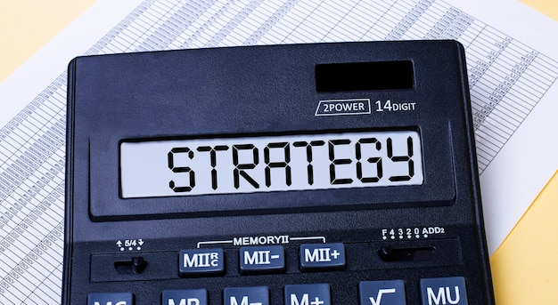 A calculator labeled strategy is on the table near the report