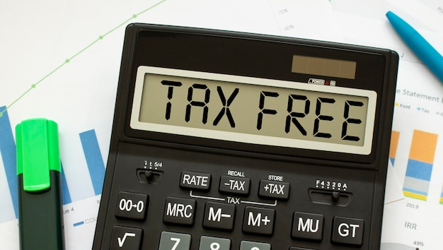 A calculator labeled tax free lies on financial documents in the office