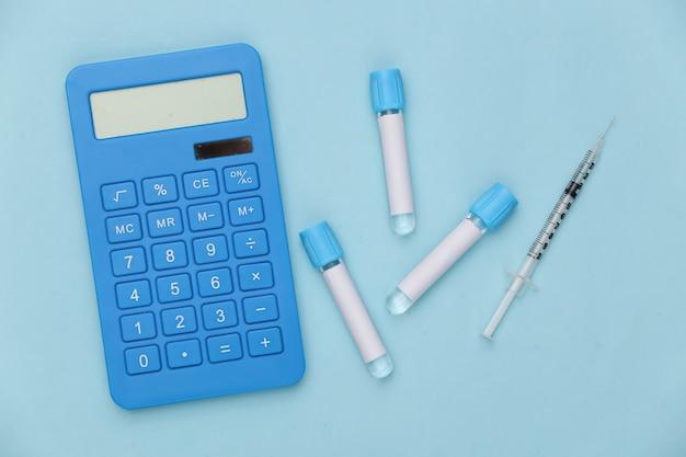 계산기, 파란색 배경에 주사기가 있는 의료 테스트 튜브. 백신 접종. 평면도