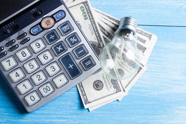 Calculator, money and light bulb on the table