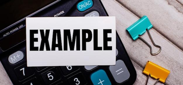 電卓、マルチカラーのペーパークリップ、明るい木製のテーブルに「example」と書かれた白いカード