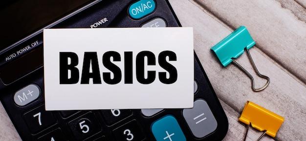 계산기, 여러 가지 빛깔의 종이 클립 및 가벼운 나무 테이블에 비문 basics와 흰색 카드. 문구 및 계산기.