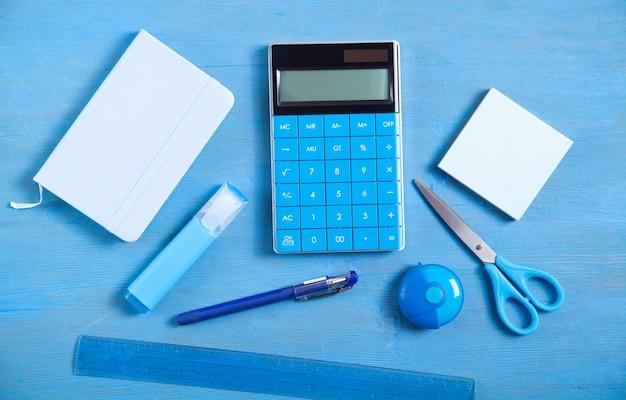 Калькулятор, записка, ластик, ножницы, ручка, маркер, заметки на синей поверхности.