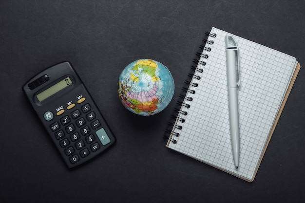 Калькулятор, ноутбук и глобус на черном фоне. вид сверху