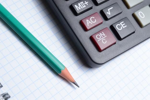 Калькулятор, блокнот и карандаш лежат вместе. крупный план.