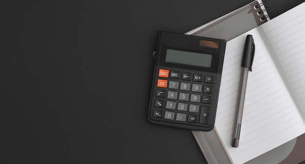 電卓、ノートブック、黒革の背景にペン。コピースペースのある上面図。フラットレイ構成。