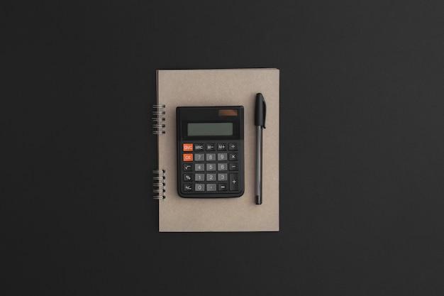 黒革の背景に電卓ノートブックペン