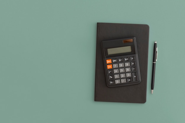 電卓、ノートブック、緑の背景にペン。学校に戻る