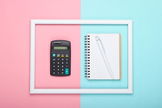 Calculator and notebook in white frame on pink blue pastel surface