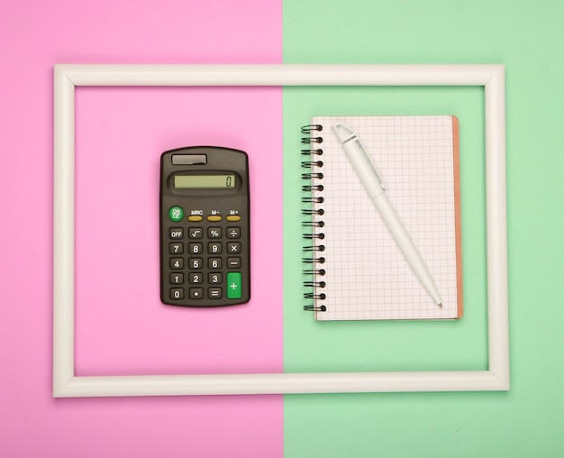 Calculator and notebook in white frame on pink green pastel surface