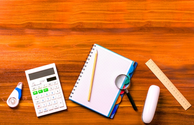 Calculator, notebook with a spring, ruler, magnifier, pencil, stapler on a wooden table