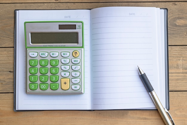 Calculator on notebook on wooden table