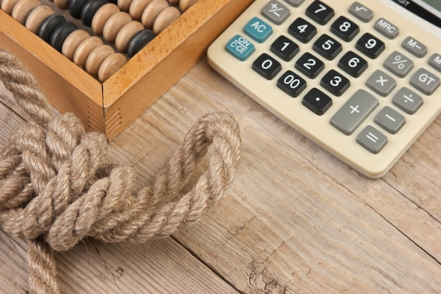 Calculator and old abacus on a wooden background