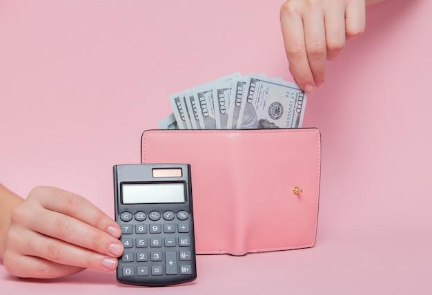 Калькулятор на фоне с женской рукой, снимающей деньги из бумажника на розовом