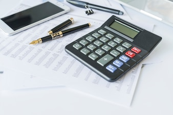 Calculator on desk with documents and smartphone