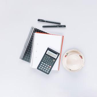 Калькулятор на спиральном ноутбуке с ручкой и пустой керамической чашкой на белом фоне
