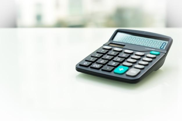 Калькулятор на белом столе возле окна