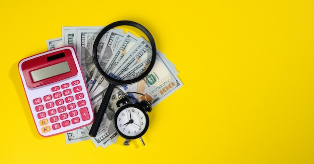 Calculator, paper american hundred dollar bills and a magnifying glass on a yellow background. the concept of search for earnings, profit with less time, reward. baner