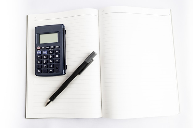 Calculator and pen on a blank book