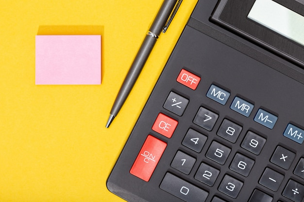 Calculator, pen and blank sticky note on yellow background. economy or business concept background. copy space. mock up