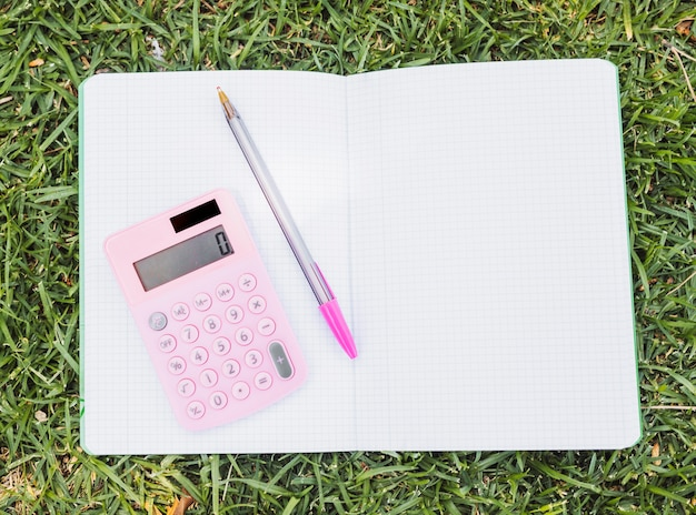 Calculator and pen on top of opened notebook