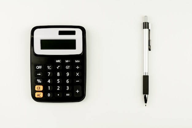 Calculator and and a pen on white table. - top view with copy space.