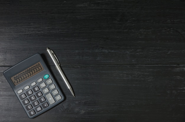A calculator and pen on wooden background with copy space for insert text.