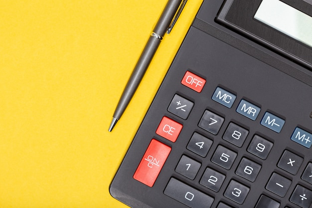 Calculator and pen on yellow background. economy or business concept background