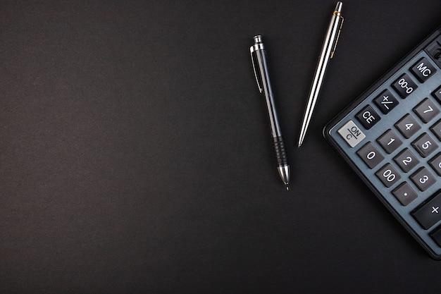 Калькулятор, карандаш и ручка, изолированные на черном фоне
